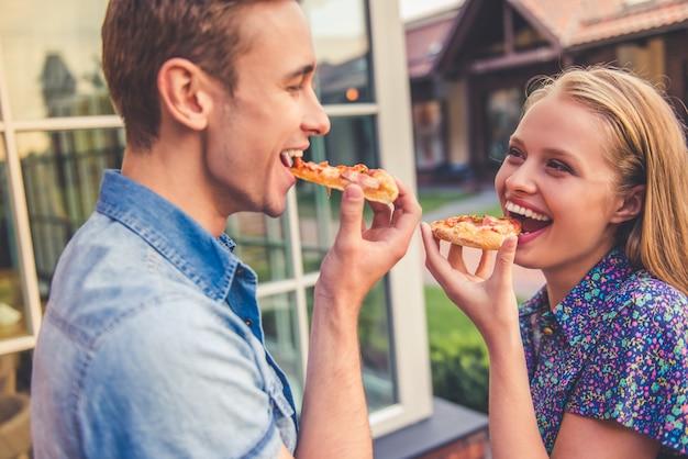 Lindo casal jovem está comendo pizza.