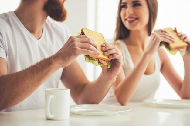 Lindo casal jovem está comendo sanduíches.