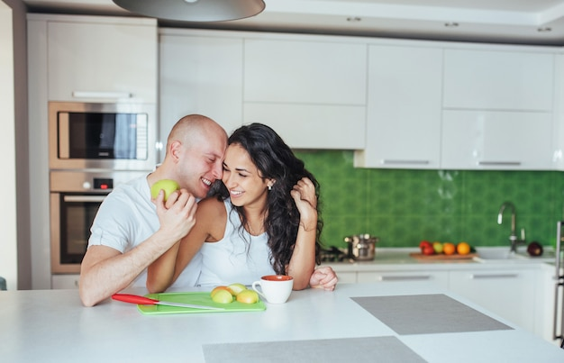 Lindo casal jovem está falando, olhando para a câmera e sorrindo enquanto cozinhava na cozinha.