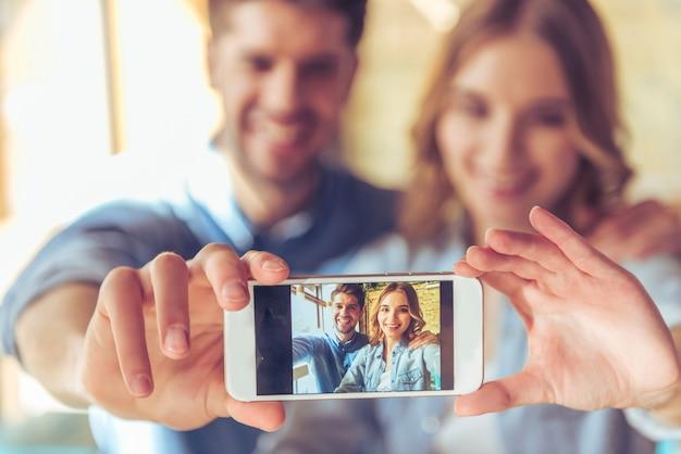 Lindo casal jovem está fazendo selfie usando um smartphone.