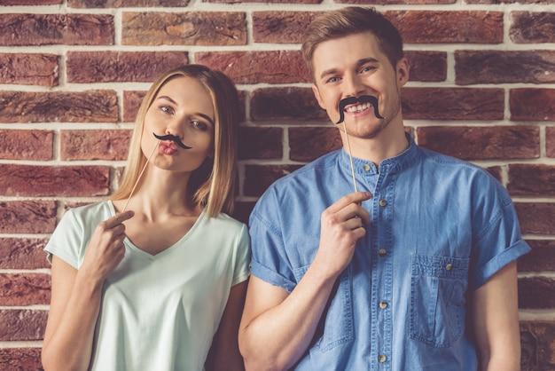 Lindo casal jovem está segurando adereços de festa em varas