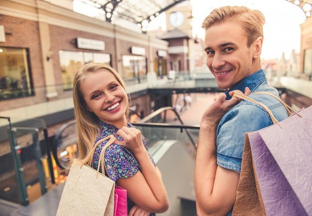 Lindo casal jovem está segurando sacolas de compras