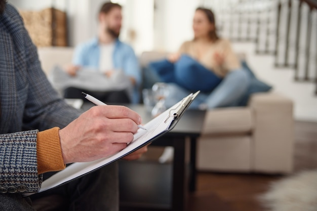 Lindo casal jovem está sentado no sofá e conversando com o psicólogo enquanto médico está fazendo anotações