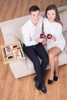 Lindo casal jovem está sentados juntos.