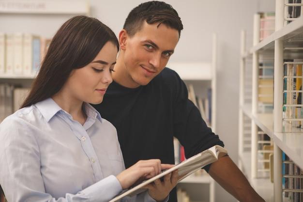 Lindo casal jovem faculdade lendo juntos na biblioteca