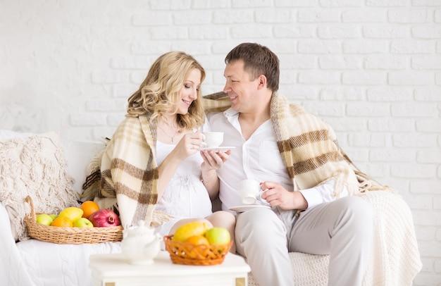 Lindo casal jovem grávida tomando café da manhã em casa com manta coberta