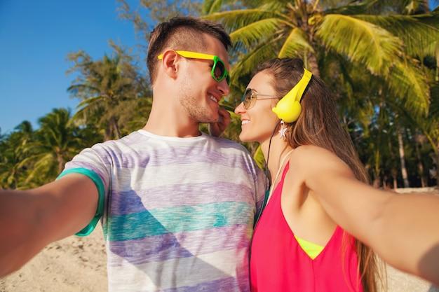 Lindo casal jovem hippie apaixonado fazendo selfie foto em uma praia tropical, férias de verão, felizes juntos, lua de mel, estilo colorido, óculos de sol, fones de ouvido, sorrindo, feliz, se divertindo, positivo
