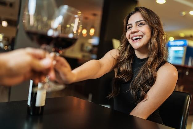 Lindo casal jovem latino com taças de vinho tinto em restaurante