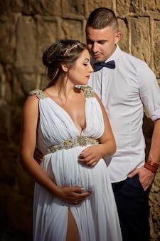 Lindo casal jovem, marido e mulher grávida em um vestido de renda branca nos braços um do outro
