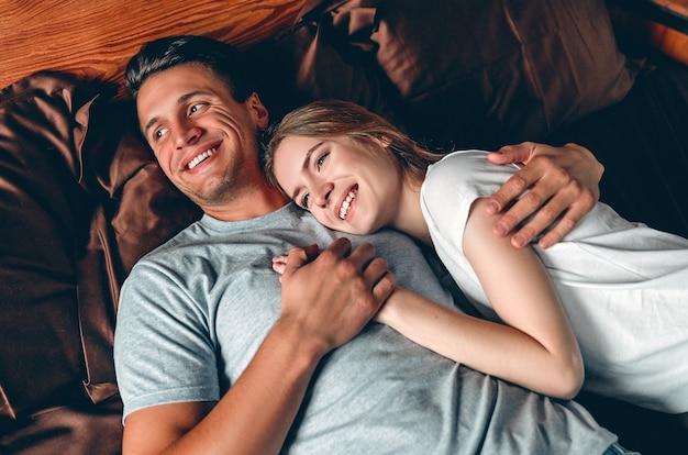 Lindo casal jovem no quarto deitado na cama