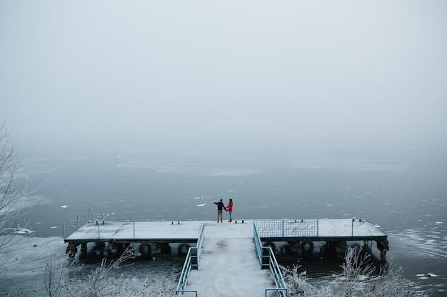 Lindo casal jovem parado em um píer olhando para o lago congelado