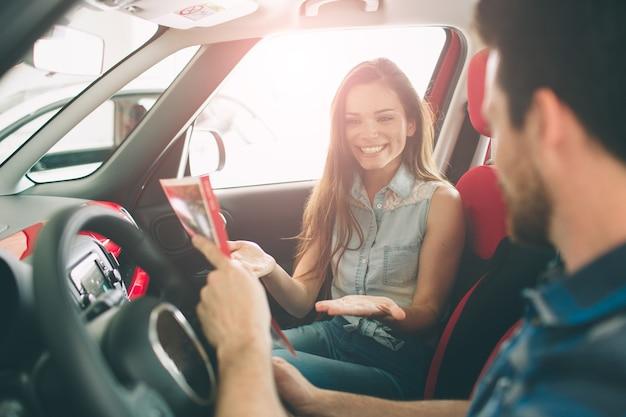 Lindo casal jovem parado na concessionária escolhendo o carro para comprar