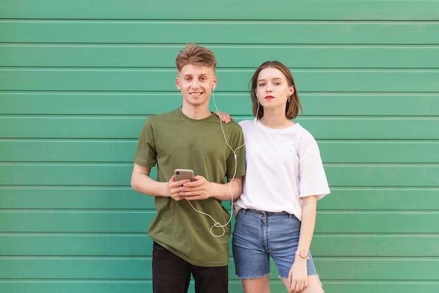 Lindo casal jovem parado na frente de uma parede verde com fones de ouvido