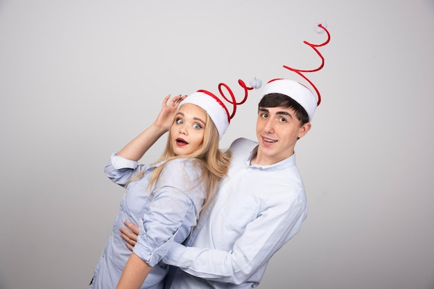 Lindo casal jovem posando com chapéus de papai noel na parede cinza.