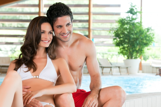 Lindo casal jovem relaxando junto à beira de uma piscina no centro de spa