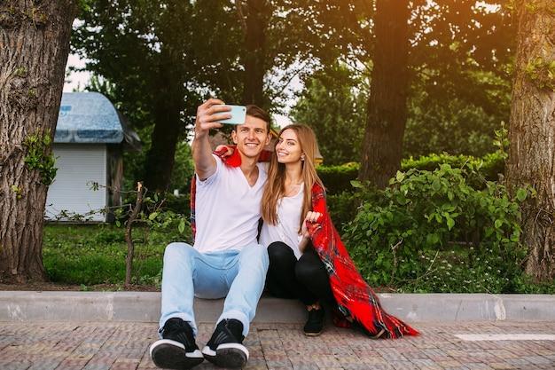 Lindo casal jovem relaxando no parque e fazendo selfie