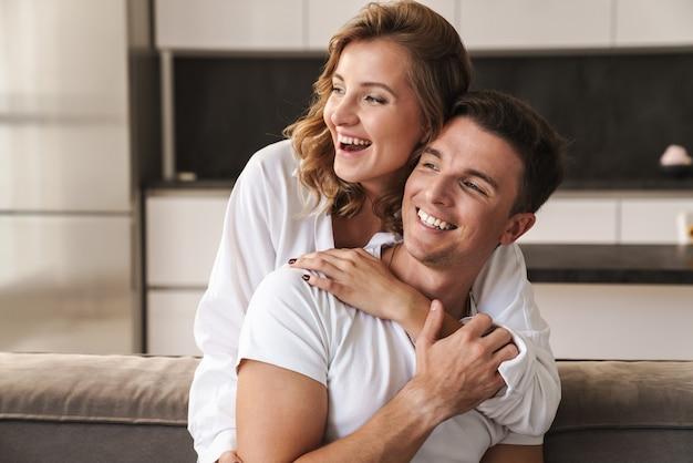 Lindo casal jovem relaxando no sofá da sala, se abraçando