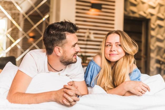 Lindo casal jovem relaxante na cama