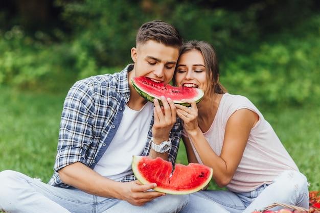 Lindo casal jovem saudável com comida saudável. melancia e verão.