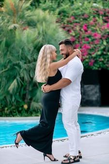 Lindo casal jovem se abraçando perto da piscina