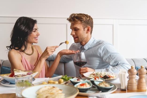 Lindo casal jovem sentado à mesa com comida deliciosa e vinho no restaurante