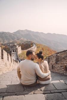 Lindo casal jovem sentado e mostrando carinho na grande muralha da china.