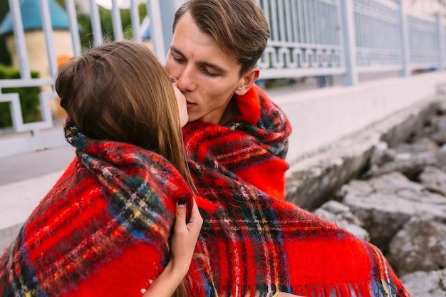 Lindo casal jovem sentado em um aterro de pedra, enrolado em um cobertor
