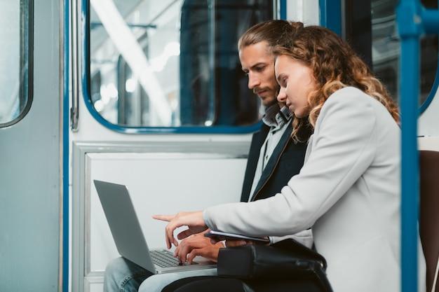 Lindo casal jovem sentado em um vagão de metrô
