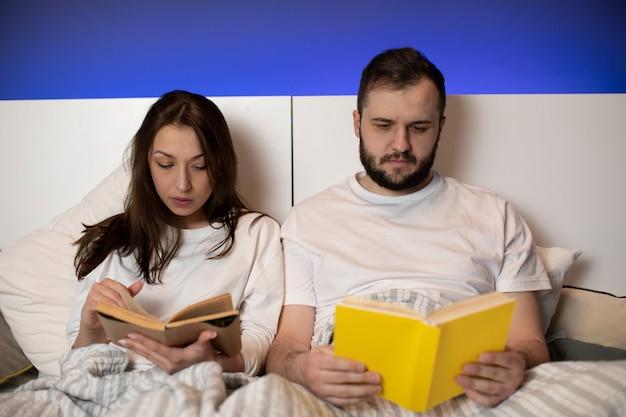 Lindo casal jovem sentado na cama lendo livros em casa no quarto