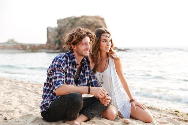 Lindo casal jovem sentado na praia juntos