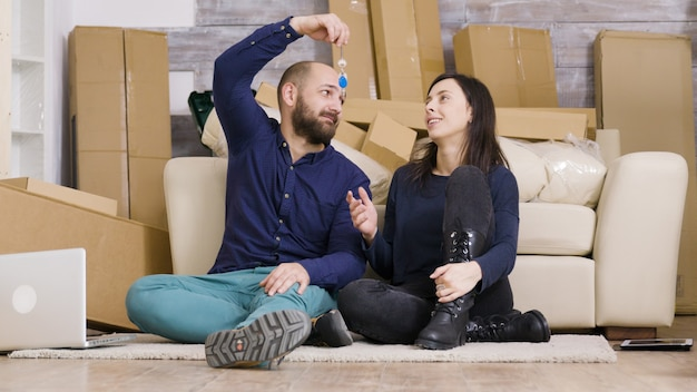 Lindo casal jovem sentado no chão de seu novo apartamento. namorado dando as chaves para a namorada dela. caixas de papelão.
