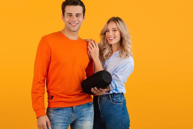 Lindo casal jovem sorridente segurando alto-falante sem fio, ouvindo música estilo colorido, feliz humor isolado em fundo amarelo