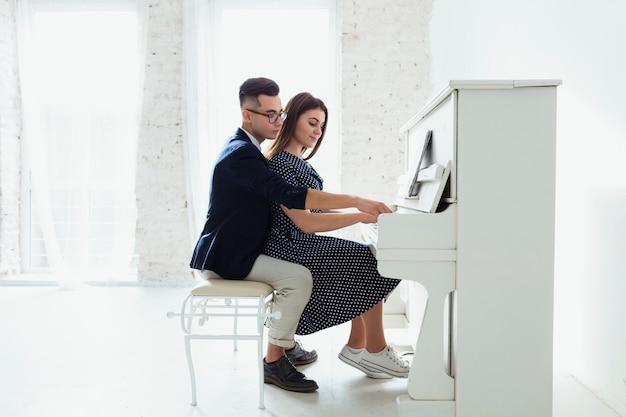 Lindo casal jovem tocando piano juntos em casa
