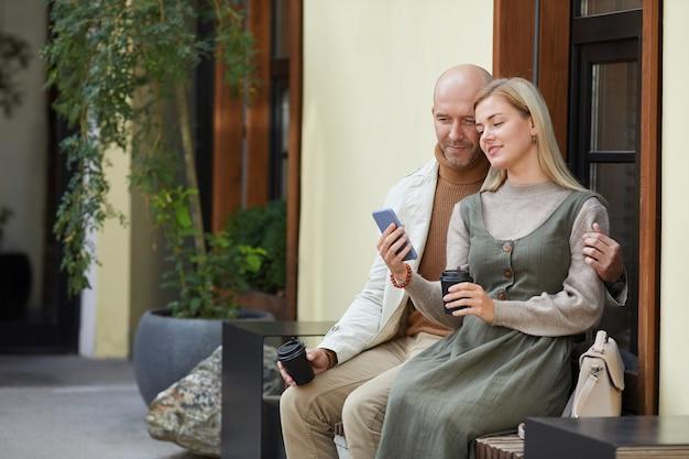 Lindo casal jovem tomando café e vendo fotos no celular, sentados ao ar livre na cidade