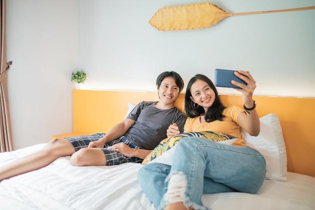 Lindo casal jovem usando smartphone e sorrindo enquanto passa um tempo na cama em casa