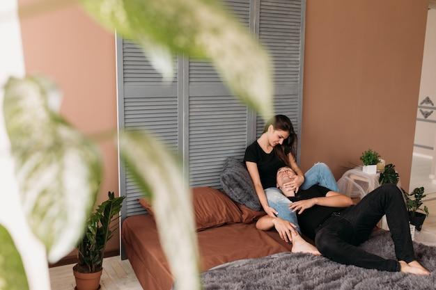 Lindo casal jovem vestido em estilo casual senta-se no chão na acolhedora sala moderna