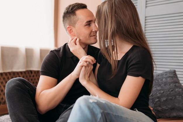 Lindo casal jovem vestido em estilo casual senta-se no chão