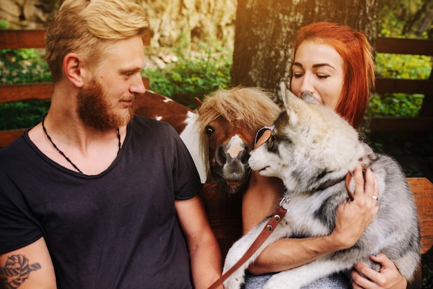 Lindo casal junto com um cachorro descansando em um balanço. foto do casal de um ângulo próximo. ao lado do pônei