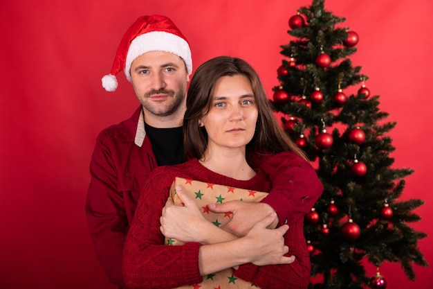 Lindo casal lindo posando em casa na frente da árvore de natal, celebrando o ano novo, homem com chapéu de papai noel e jovem mulher com o presente de natal em fundo vermelho.