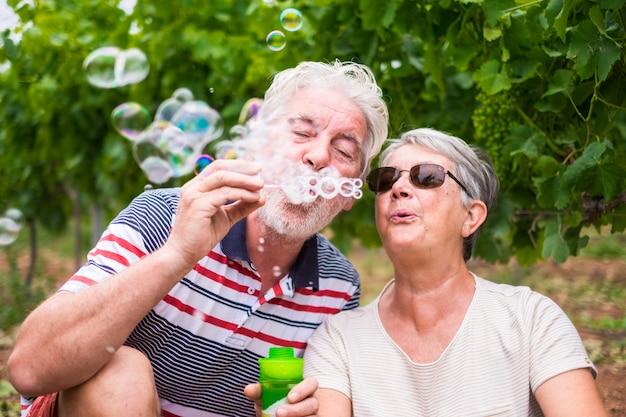 Lindo casal maduro caucasiano, homem e mulher, fazem bolhas de sabão juntos para brincar e se divertir com alegria, natureza ao ar livre local para atividades de lazer feliz para aposentados com estilo de vida