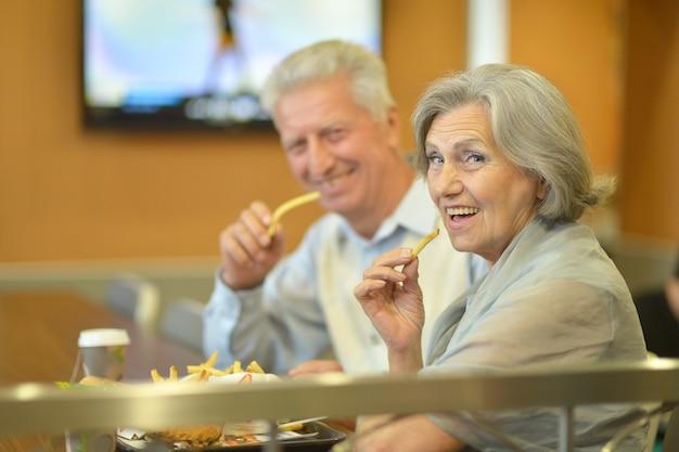 Lindo casal maduro comendo batatas fritas em um café