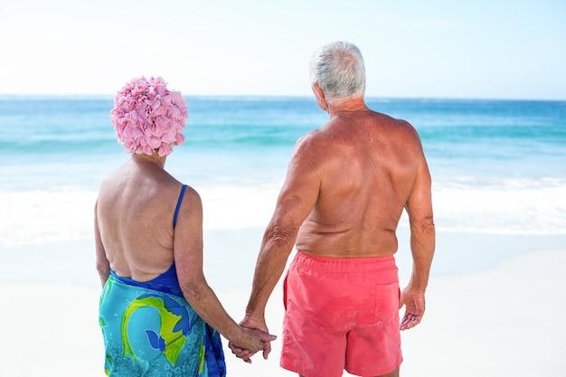 Lindo casal maduro de mãos dadas na praia