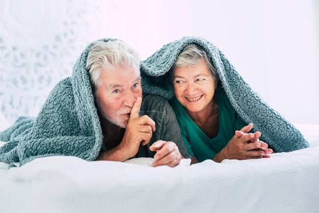 Lindo casal maduro lindo e feliz no quarto, deitar na cama, ficar embaixo da coberta e dizer silêncio para a câmera