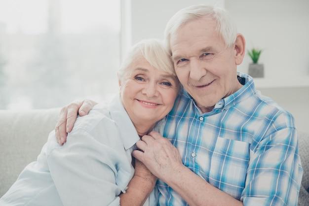 Lindo casal mais velho posando juntos no sofá