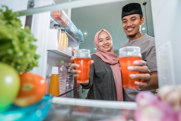 Lindo casal muçulmano quebrando o iftar de jejum em frente à geladeira aberta na cozinha bebendo