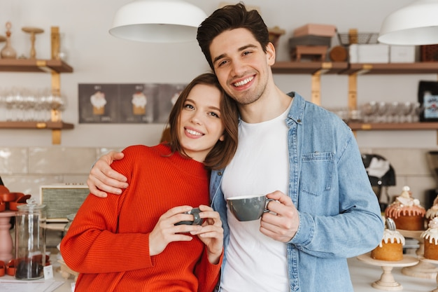 Lindo casal, mulher e homem em roupas casuais, sorrindo e em pé com xícaras de café em um café aconchegante
