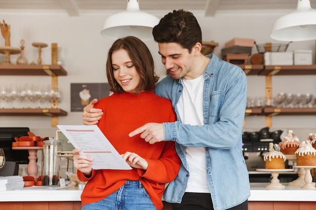 Lindo casal mulher e homem sorrindo e lendo o menu, enquanto namoram em um restaurante