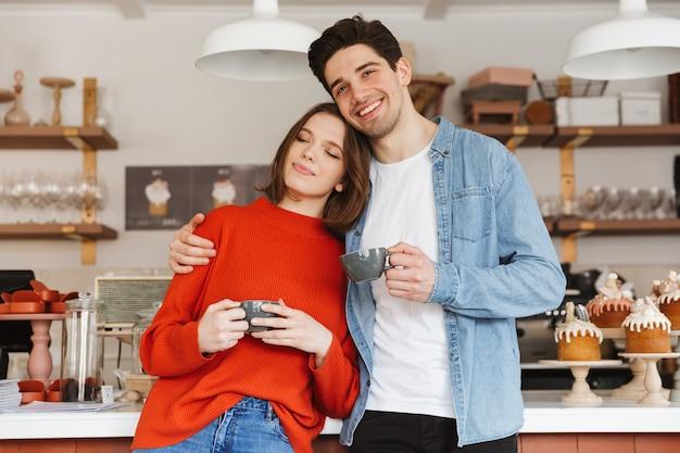 Lindo casal mulher e homem sorrindo na padaria, segurando copos com café nas mãos