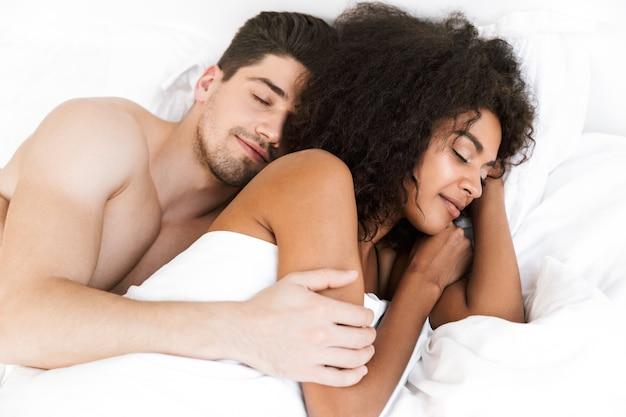 Lindo casal multiétnico jovem e feliz relaxando na cama, debaixo do cobertor, mulher dormindo