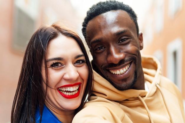 Lindo casal multiétnico se divertindo na rua.